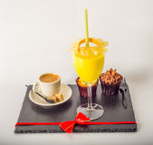 Ensemble de café noir dans une tasse, deux petits pains avec une boisson jaune dedans Image libre de droits