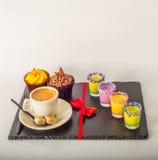 Ensemble de café noir dans une tasse, deux petits pains avec une boisson jaune dedans Image stock