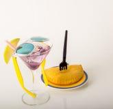Ensemble de café noir dans une tasse, deux petits pains avec une boisson jaune dedans Photographie stock libre de droits