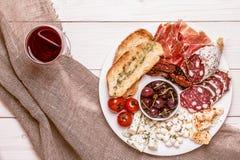 Ensemble de casse-croûte de vin Variété de fromage et de viande, olives, tomates dessus Image libre de droits
