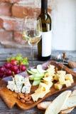 Ensemble de casse-croûte de vin Verre de vin blanc, de raisin et de divers che de sortes Photographie stock