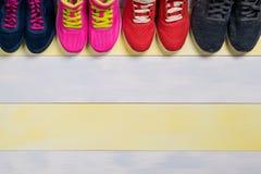 Ensemble de chaussures de sports sur un beau fond gris jaune du plancher dans le hall Photographie stock