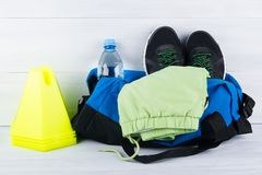 Ensemble de choses de sports pour jouer des sports, des chaussures de course et une forme dans un sac et une bouteille de l'eau,  Photo libre de droits