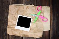 Ensemble de ciseaux de cadre de photo et de papier chiffonné sur le fond en bois Image libre de droits