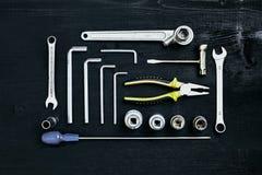 Ensemble de clé d'outils de clé et de tournevis de prise de pinces sur le fond en bois noir Image stock