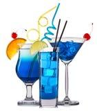 Ensemble de cocktails bleus avec la décoration des fruits et de la paille colorée sur le fond blanc Photo libre de droits