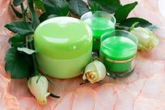 Ensemble de cosmétique de 3 bouteilles crèmes dans les roses Photo stock