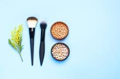 Ensemble de cosmétiques décoratifs pour le correcteur Brushes de fard à joues de poudre de maquillage sur le fond bleu Configurat Images stock