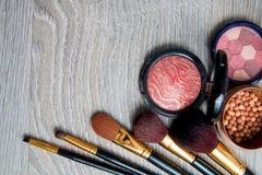 Ensemble de cosmétiques et de brosses décoratifs sur le fond en bois gris Divers produits de maquillage de bruns Vue supérieure,  Photo stock