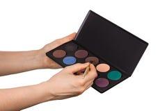 Ensemble de cosmétiques de maquillage pour le maquillage et de brosse dans des mains femelles d'isolement sur le blanc Photos libres de droits
