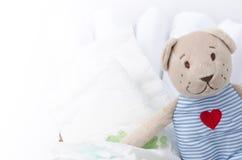 Ensemble de couches-culottes pour nouveau-né dans le panier avec le jouet d'ours d'amour Cl de bébé Photographie stock libre de droits