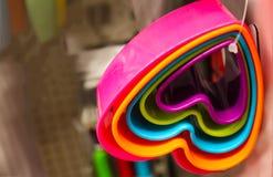 Ensemble de coupeurs brillamment colorés en forme de coeur de biscuit pendant d'un lien en plastique sur le fond brouillé photographie stock libre de droits