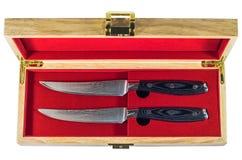 Ensemble de couteau de bifteck dans une boîte en bois d'isolement sur le fond blanc Photos stock