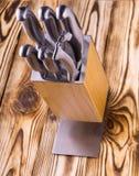Ensemble de couteaux de cuisine brillants en métal sur une table en bois Photographie stock