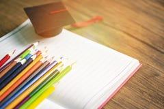 Ensemble de crayon et chapeau color?s d'obtention du dipl?me sur le carnet de livre blanc de nouveau ? l'?cole et au concept d'?d photo stock
