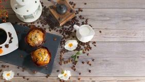 Ensemble de deux petits pains, de tasse de café d'arome, de cruche de crème au café et de chandelier sur le fond en bois gris ave photos libres de droits