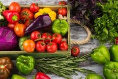 Ensemble de différents légumes colorés crus frais dans le plateau en bois, fond en bois clair Photo stock