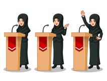 Ensemble de femme d'affaires dans le costume noir avec le voile donnant un discours derrière l'estrade Photographie stock