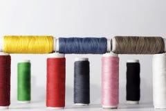 Ensemble de fils de couture colorés sur le fond blanc Images stock