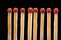 Ensemble de huit matchs en bois rouges sur le fond noir Photos libres de droits