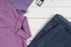 Ensemble de l'habillement et des chaussures des hommes sur le fond en bois Sports T-shirt et espadrilles dans des couleurs lumine Photographie stock