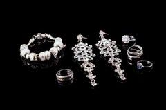Ensemble de luxe de bijoux Anneaux d'or blanc ou d'argent, boucles d'oreille avec des cristaux et pendant d'isolement sur le noir Images libres de droits