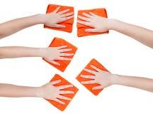 Ensemble de mains avec des chiffons oranges de microfibre d'isolement Photos stock