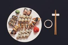 Ensemble de maki et de petits pains de sushi au bois rustique noir Photo stock