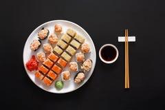 Ensemble de maki et de petits pains de sushi au fond noir Photos stock