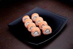 Ensemble de maki Philadelphie de sushi de plat noir Nourriture japonaise sur le fond Image stock