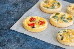 Ensemble de mini tartes savoureuses sur un papier de cuisson WI végétaux de quiches Image libre de droits
