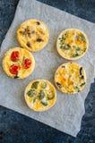 Ensemble de mini tartes savoureuses sur un papier de cuisson WI végétaux de quiches photo stock