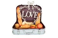 Ensemble de pain dans le bagage de voyage avec amour sur le blanc Images stock