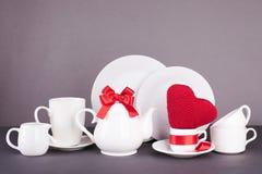 Ensemble de plats blancs pour le déjeuner et le thé avec des éléments de décor des coeurs rouges et de rubans de satin sur un fon Photographie stock libre de droits