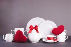 Ensemble de plats blancs pour le déjeuner et le thé avec des éléments de décor des coeurs rouges et de rubans de satin sur un fon Photos libres de droits