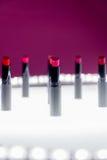 Ensemble de rouge à lèvres mat dans des couleurs rouges et naturelles sur le fond blanc et rose Rouges à lèvres colorés de mode M Images libres de droits