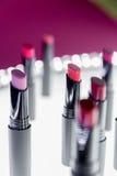 Ensemble de rouge à lèvres mat dans des couleurs rouges et naturelles sur le fond blanc et rose Rouges à lèvres colorés de mode M Image libre de droits