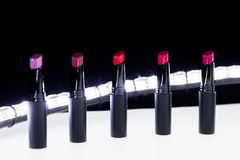 Ensemble de rouge à lèvres mat dans des couleurs rouges et naturelles sur le fond blanc et noir Rouges à lèvres colorés de mode M Photos libres de droits
