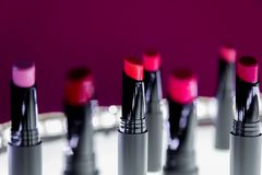 Ensemble de rouge à lèvres mat dans des couleurs rouges et naturelles sur le fond blanc et rose Rouges à lèvres colorés de mode M Photographie stock
