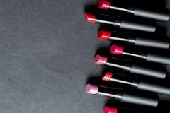 Ensemble de rouge à lèvres mat dans des couleurs rouges et naturelles sur le fond noir Rouges à lèvres colorés de mode Beauté pro Image stock