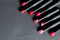 Ensemble de rouge à lèvres mat dans des couleurs rouges et naturelles sur le fond noir Rouges à lèvres colorés de mode Maquillage Photos libres de droits