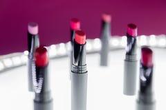 Ensemble de rouge à lèvres mat dans des couleurs rouges et naturelles sur le fond rose blanc Rouges à lèvres colorés de mode Beau Image stock