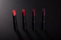 Ensemble de rouges à lèvres rouges sur le fond noir Photographie stock libre de droits