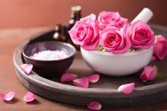 Ensemble de station thermale avec du sel rose d'huiles essentielles de mortier de fleurs Photographie stock libre de droits