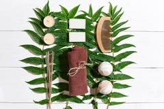 Ensemble de station thermale avec la serviette et le savon sur le fond en bois blanc avec les feuilles vertes Image stock