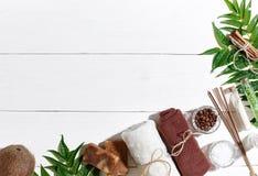 Ensemble de station thermale avec la serviette et le savon sur le fond en bois blanc avec les feuilles vertes Photographie stock