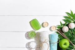 Ensemble de station thermale avec la serviette et le savon sur le fond en bois blanc avec les feuilles vertes Photo stock