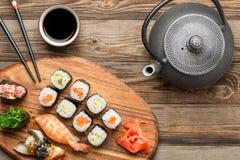 Ensemble de sushi de vue supérieure, théière et bâtons noirs Images stock