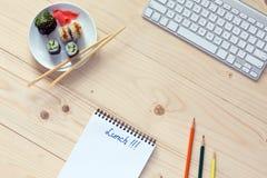 Ensemble de sushi et baguettes ordinateur et bloc-notes sur le bureau en bois Photo stock