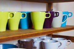 Ensemble de tasses colorées sur l'étagère Image libre de droits